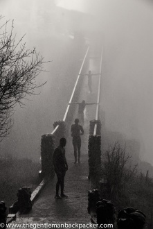 """""""Mosi Oa Tunya (The Smoke that Thunders): Ghostly figures emerge from the mist from Victoria Falls, Zambia. They are revealed to be children, using the bridge as a water slide on which to play. Zambia, May 2010."""