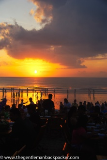 """""""Jimbaran Tradition"""":Tourists sit down to dine at one of the many restaurants that line Jimbaran Bay in Bali, Indonesia. Locals play around in the water and hawk their wares, such as fruit, live music, and balloons. June, 2011."""