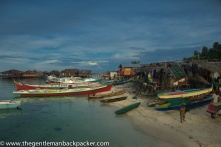"""""""Two Worlds Collide"""": Colorful boats at sunset float between a destitute shanty town and an ultra-luxurious floating villa resort on Pulau Mabul, Malaysia. Villagers live on $1 a day, while tourists spend as much as $400 a night."""