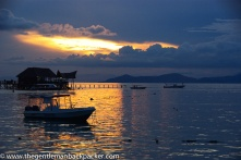 """""""In Search of Sipadan"""": At dusk, dive boats sit in the bay at Pulau Mabul, gateway to Sipadan, the holy grail of SCUBA diving off the coast of Borneo, Malaysia, while the sun, already below the horizon lights up the clouds."""
